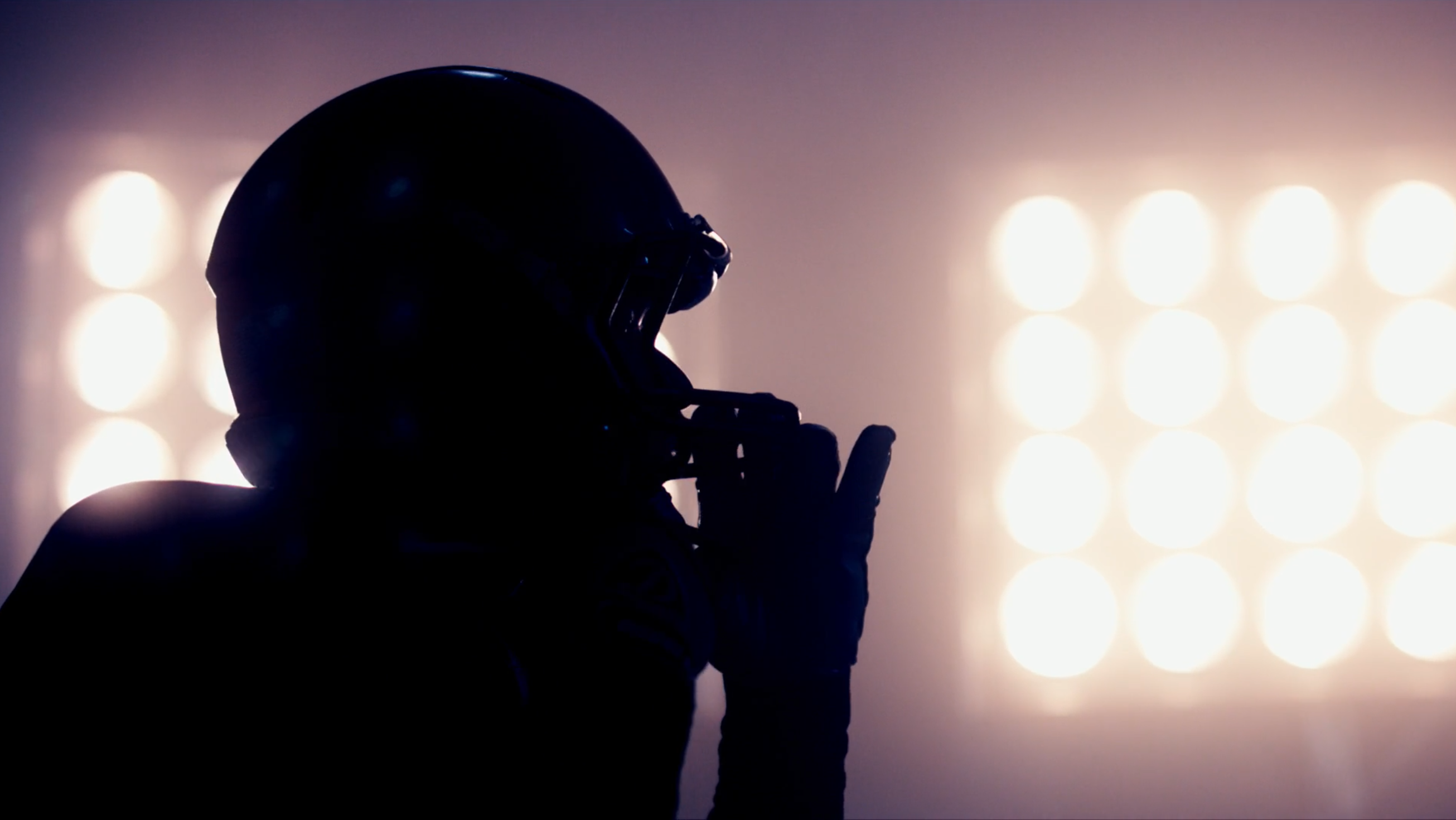 football player silhouetted by field lights